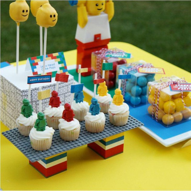 Colourful Lego party table decor idea with Lego cupcakes cake pops and gifts