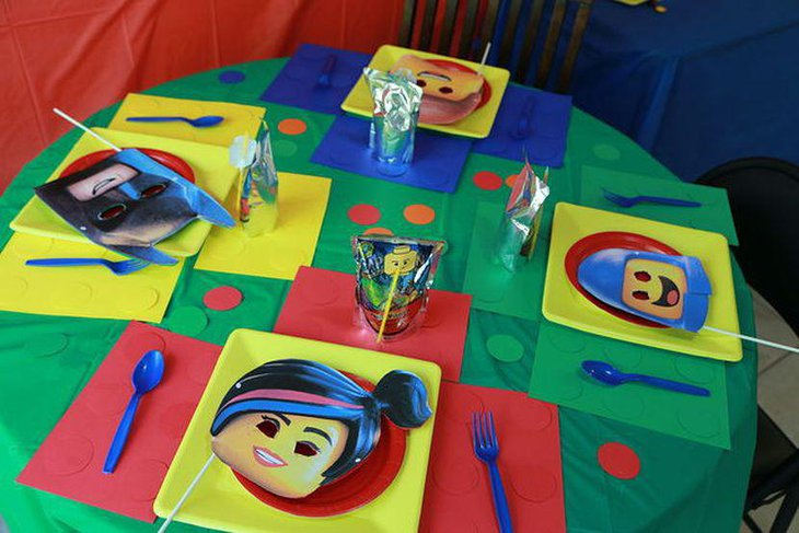 Colourful Lego party table decoration using masks square plates and Lego man printed straw covers