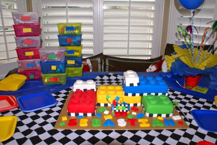 Colourful Lego themed birthday table with transparent boxes red tin pales and candy canes