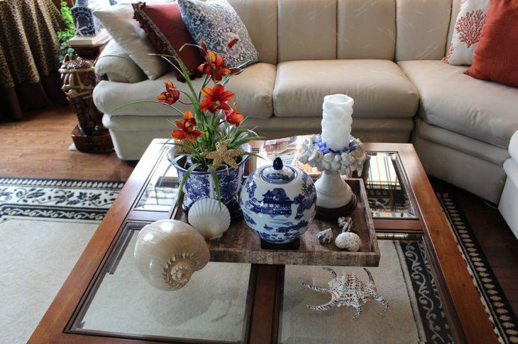 Creative coffee table vignette with shells wooden tray and shell embossed holder