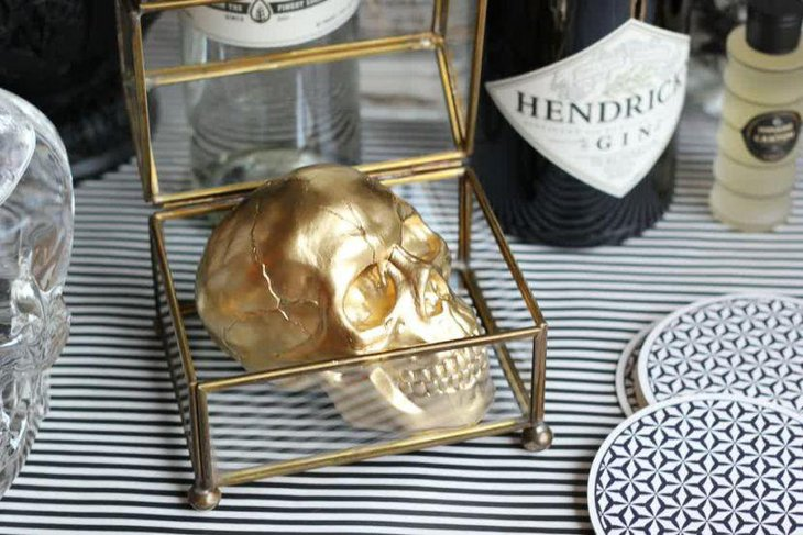 Creative golden rimmed glass box with a golden skull for Halloween table decor