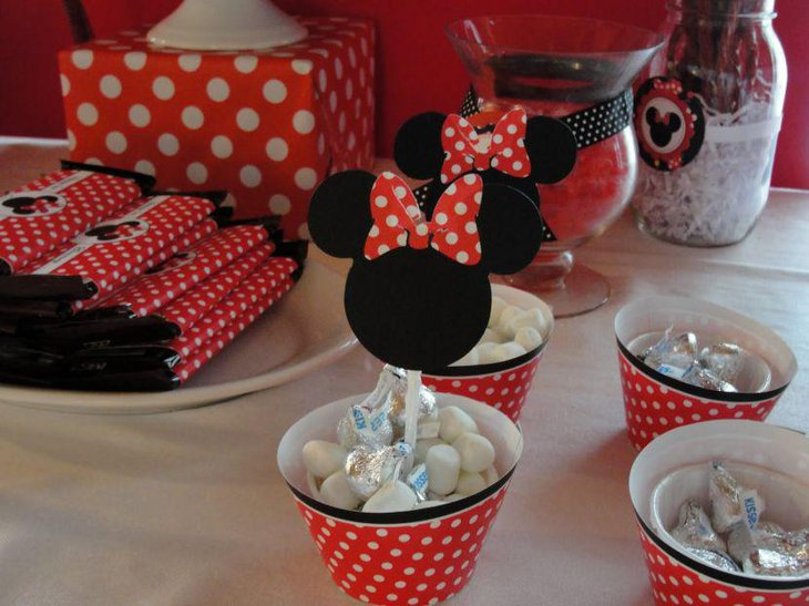 Creative Minnie Mouse polka dotted bucket decorations on candy table