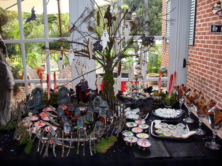 Creepy Halloween dessert table decor with ghosts hanging from a tree and a graveyard centerpiece
