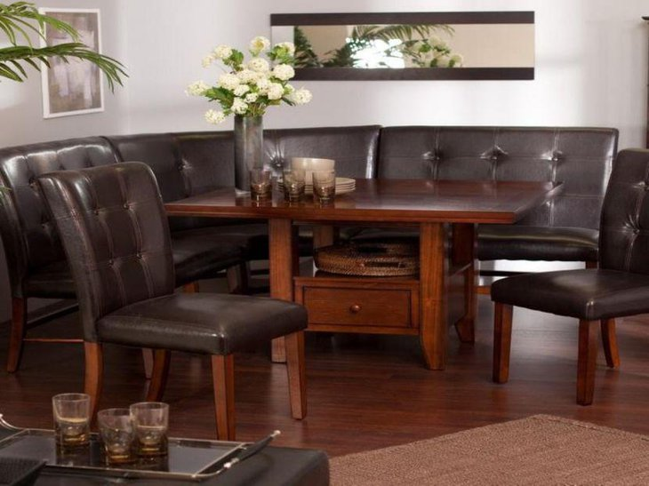 Curvy breeakfast nook with high end black leather sofas and wooden table