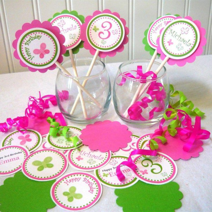 Cute pink and white DIY party table decor with glass jars wooden sticks with paper cut outs and ribbons