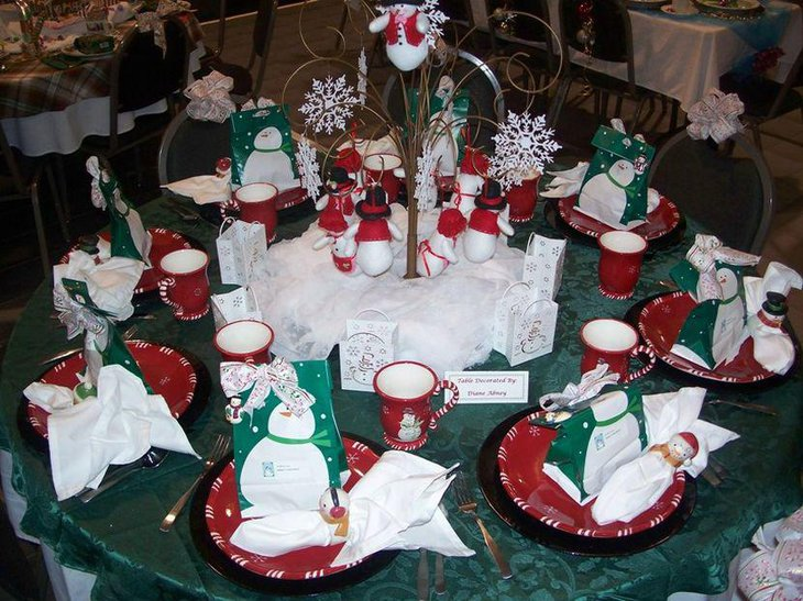 Cute snowman figurines and a tree centerpiece as Christmas party table decor