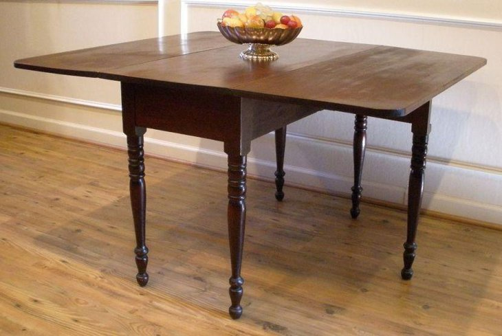 Dark antique drop leaf dining table with sleek pedestal stands