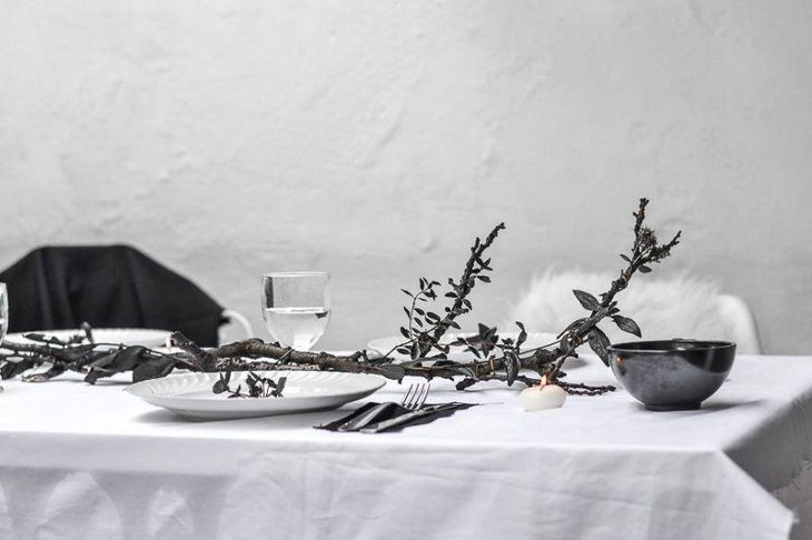Elegant DIY Halloween table decor with a black tree branch as centerpiece