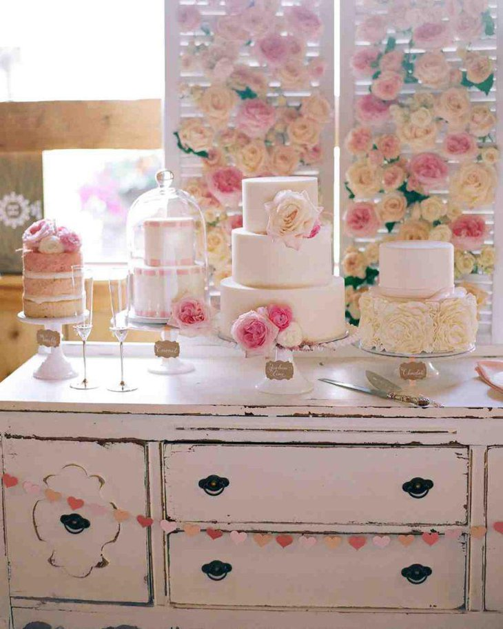 Elegant European dessert table with pink and white cake display