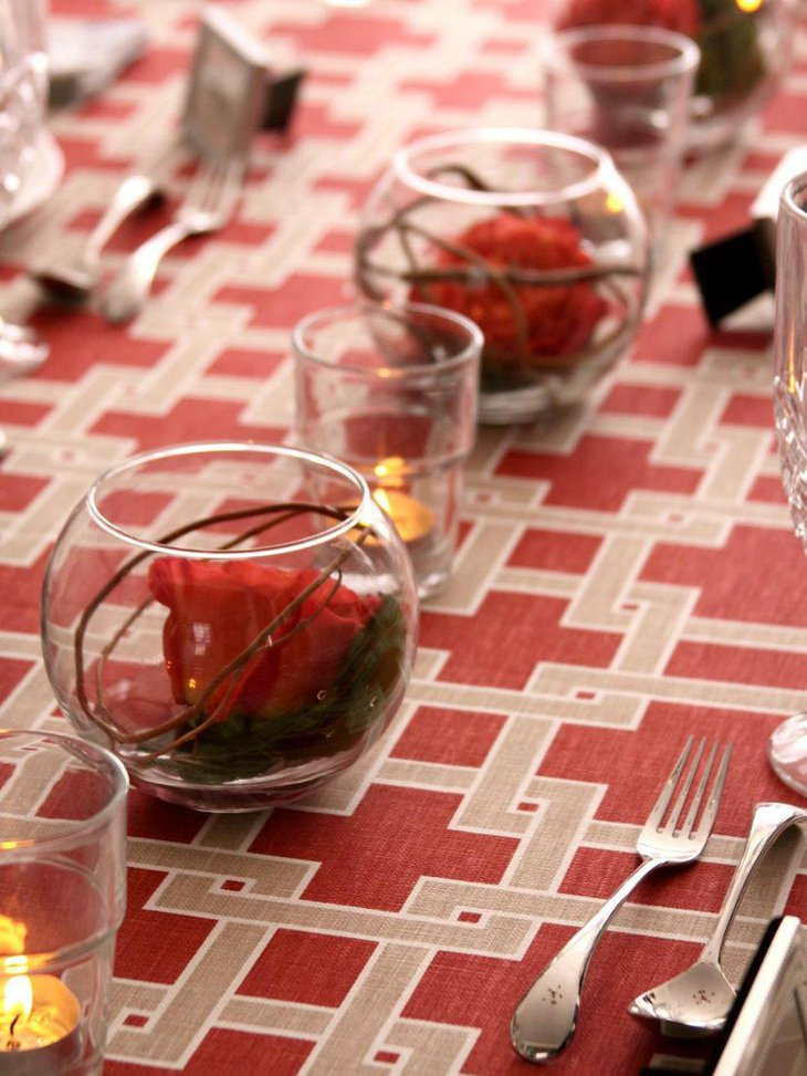 Elegant round vases with red roses and glass votives as party table centerpieces