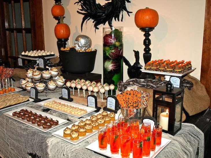 Fantastic Halloween table decor with silver skull black couldron and pumpkins on black holders