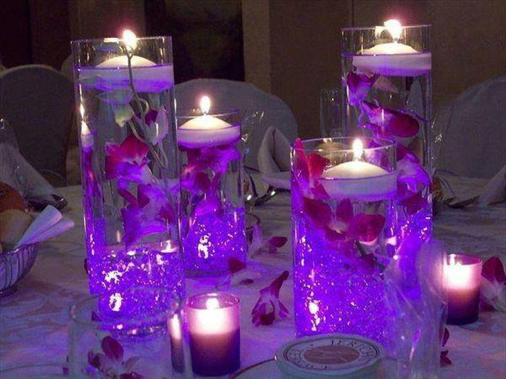 Floating candle wedding table centerpiece with purple tones