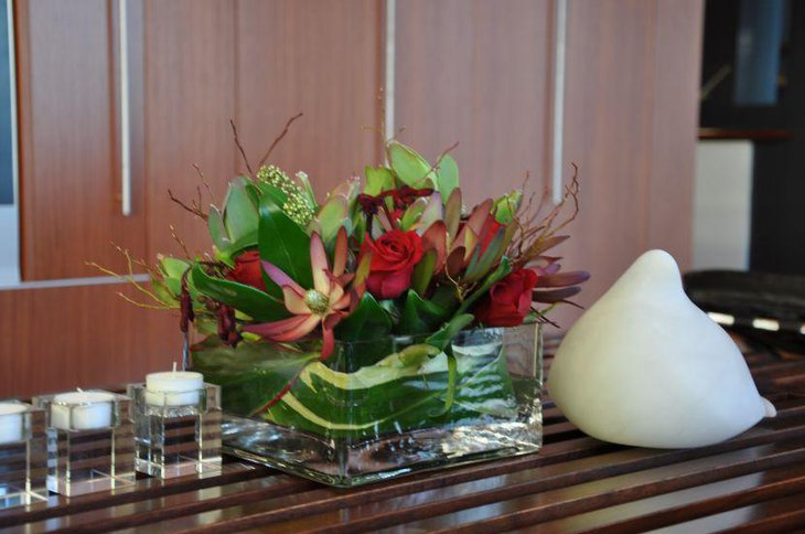 Flower blooms and green leaves in square glass vase for St Patricks Day table centerpiece
