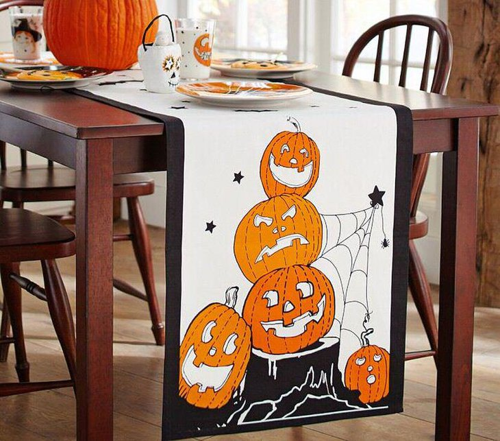Fun kids Halloween table decor with pumpkin and white and black table runner