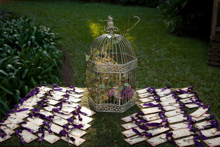 Garden wedding escort card table with purple theme