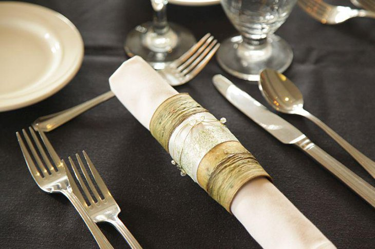 Glamorous table party setting with vintage napkins wrapped in bark golden wire and ribbon