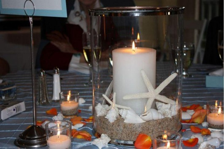 Glass candle centerpiece with sand shells and starfish