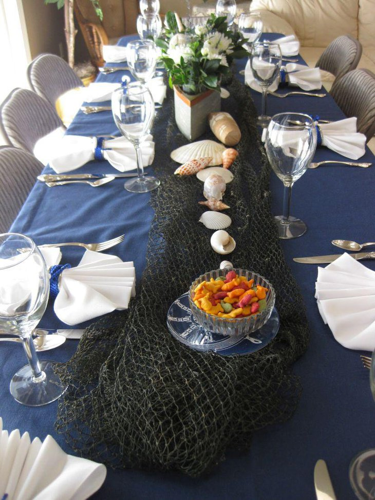 Gorgeous nautical baby shower table decor with sea shells and floral boat centerpiece