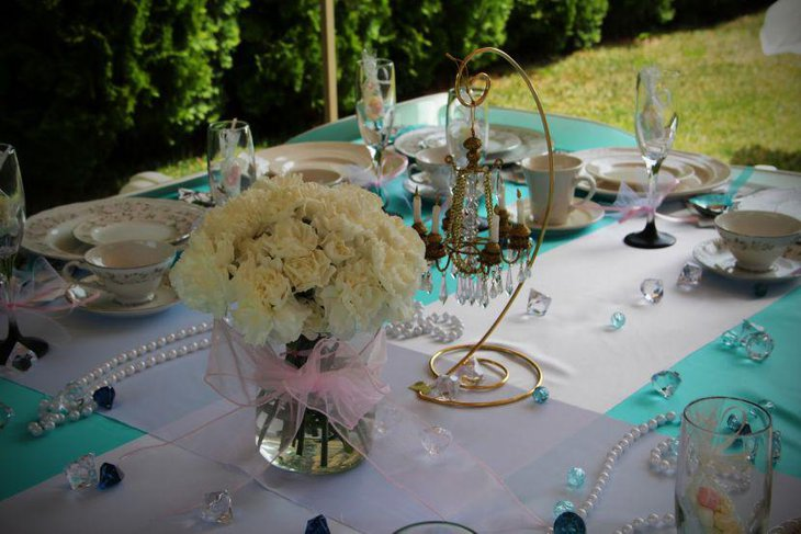 Gorgeous wedding breakfast table decor with flowers and ornamental candle holder