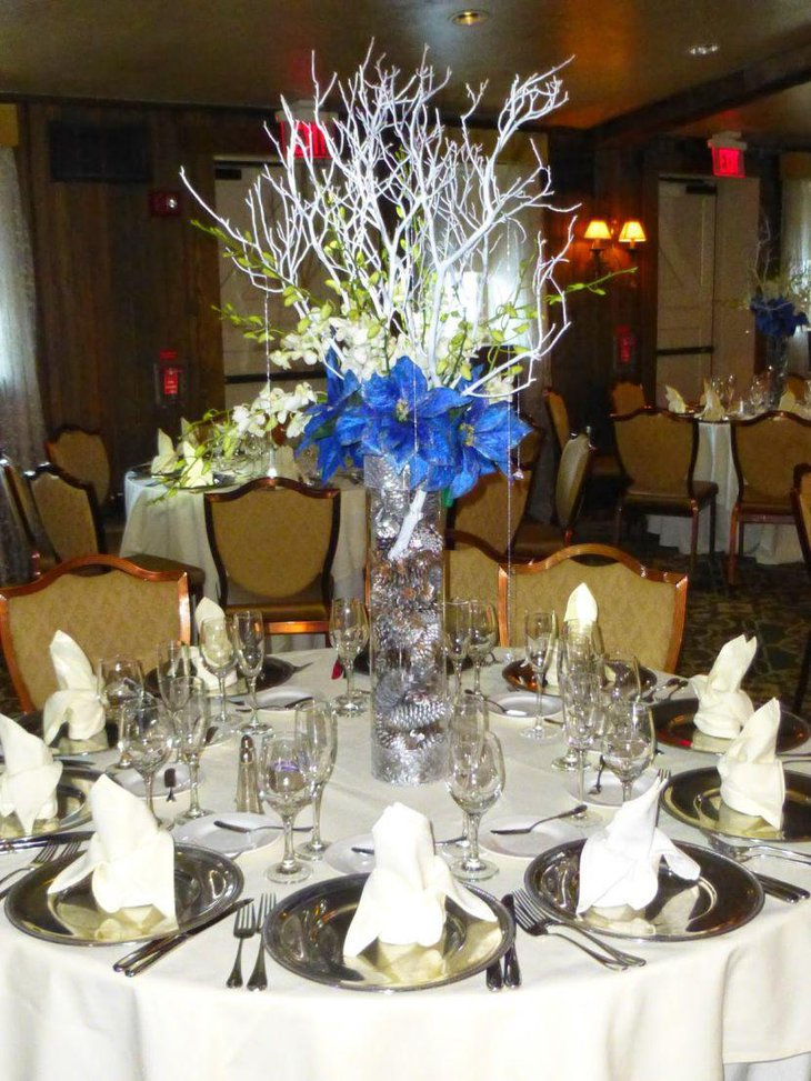 Gorgeous winter table decor with glass cylindrical vase with blue flowers