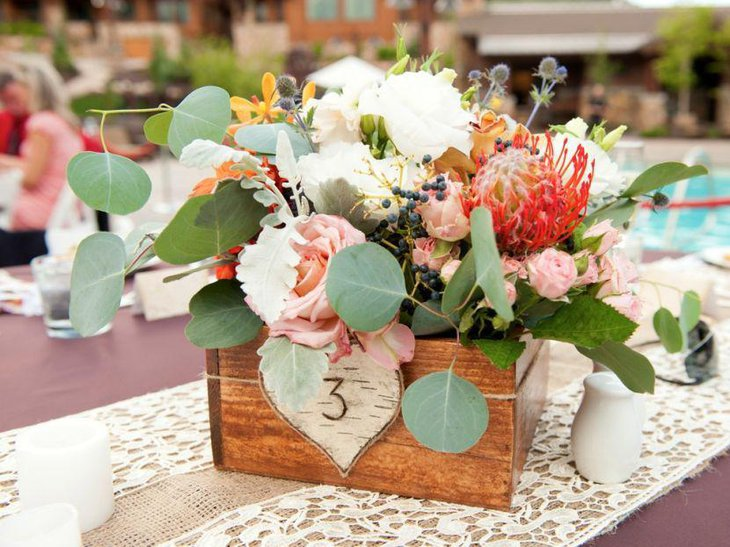 Gorgeous wooden floral centerpiece on a country wedding table