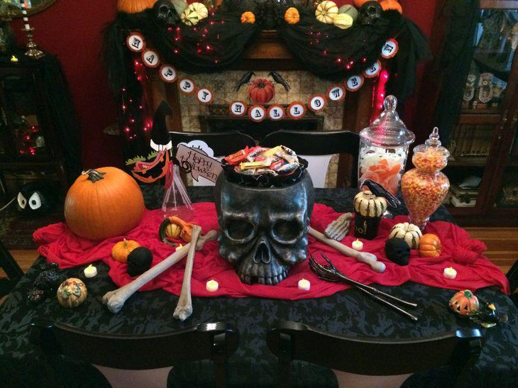 Gothic styled Halloween table with skull candy holder bones and pumpkins