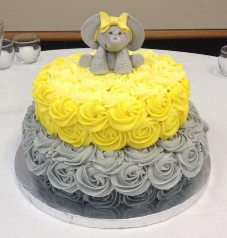 Grey and yellow rose cake with elephant on top for baby shower