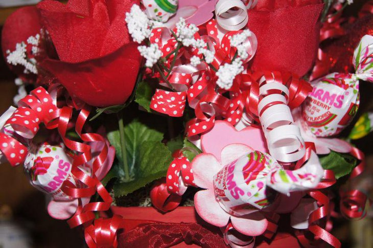 Homemade floral Valentine centerpiece with ribbons and toffies