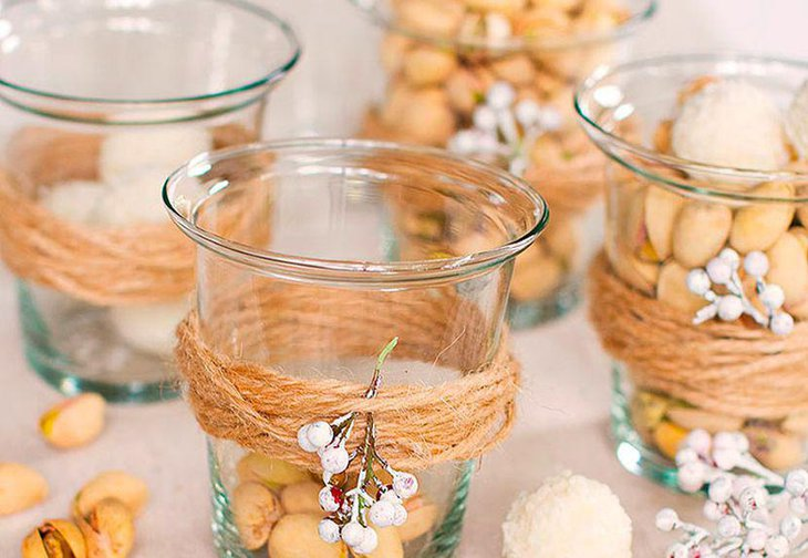 Innovative winter table decor with votives tied with twine and sprig of berries