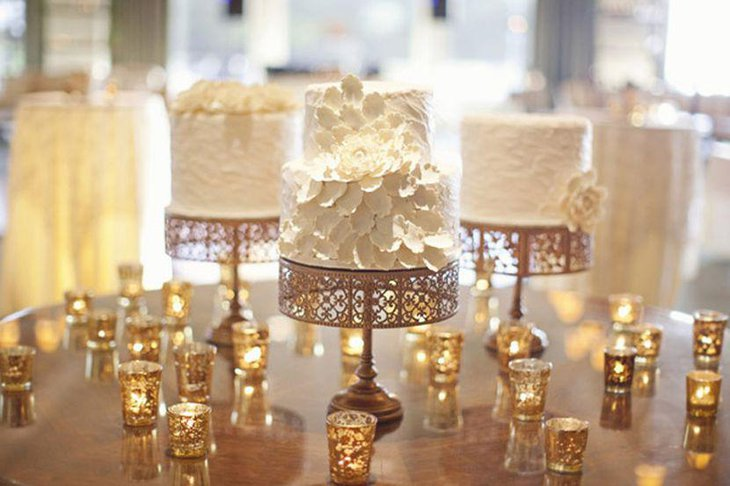 Innovative Winter wedding table setting with rich golden cakestands and mini lanterns