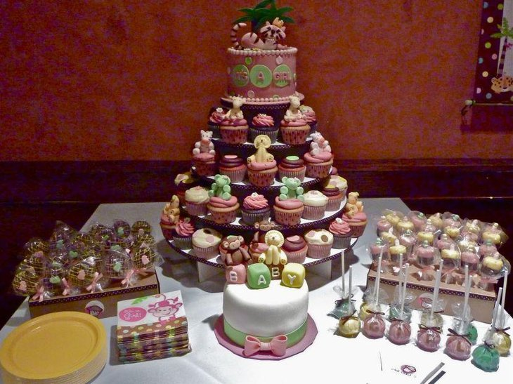 Jungle themed dessert table decorated with adorable cupcakes and candies with animal designs