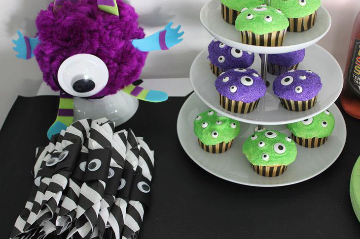 Kids Halloween party table decor with monster cupcakes and monster toy