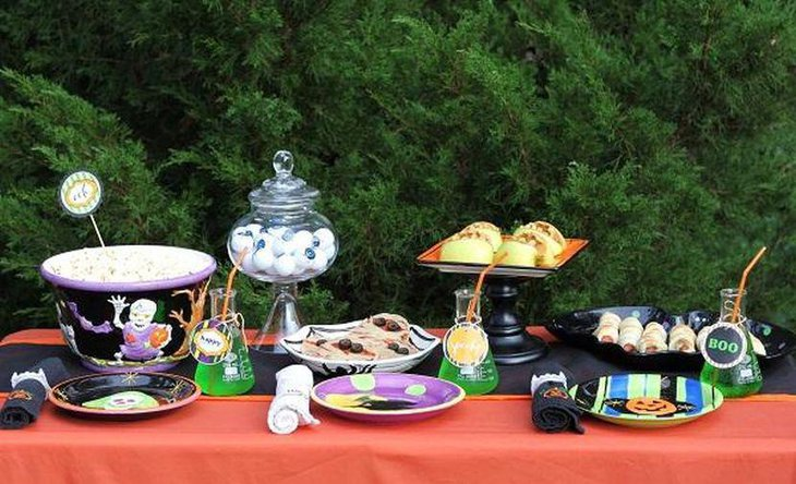 Kids Halloween party tablescape with black ghost bucket and green bottles