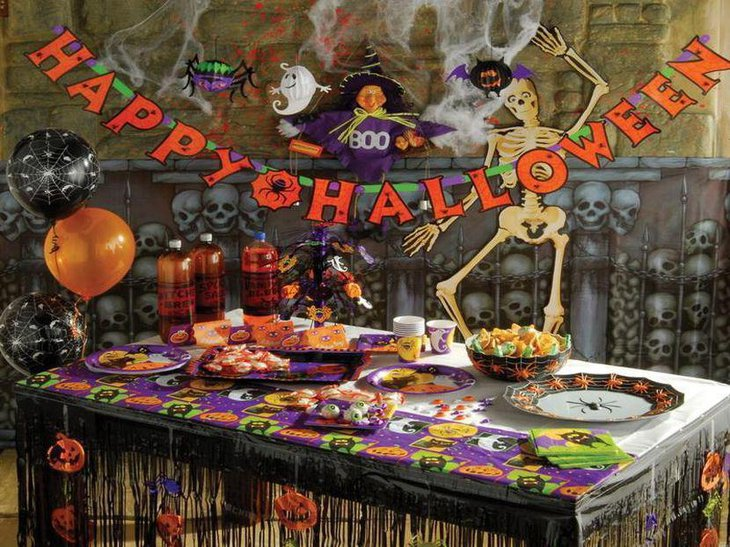 Kids Halloween table decor with spiders on plate and pumpkin cuts outs