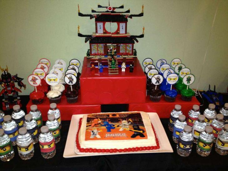 Lego Ninjago birthday party table decor with cake bottles figurines and cupcakes