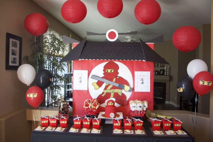 Lego Ninjago party table decor with ninjas eyes printed food packets and a red ninja cake