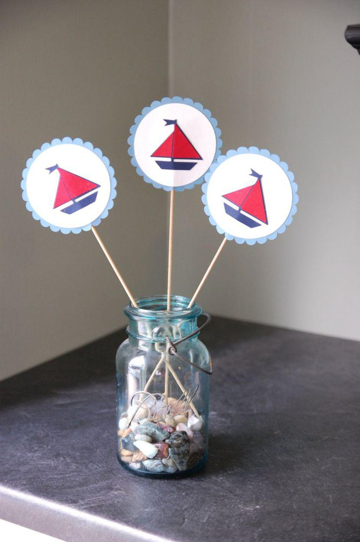 Mason jar centerpiece with red and blue sailboat sticker straws on nautical baby shower table