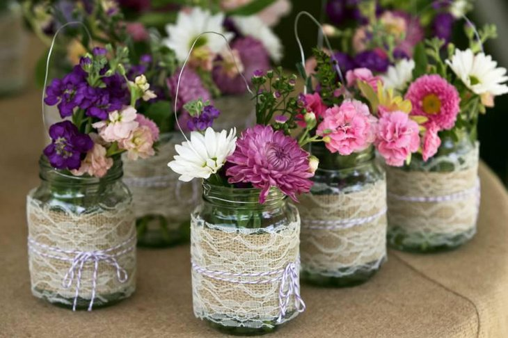 Mason Jar Containing Flowers Decorated with Burlap Lace
