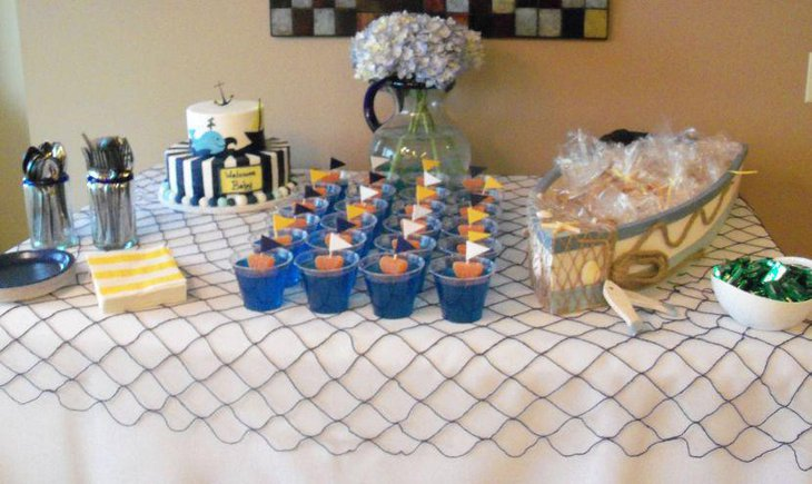 Nautical baby cake table decor with sail boat and floral jar