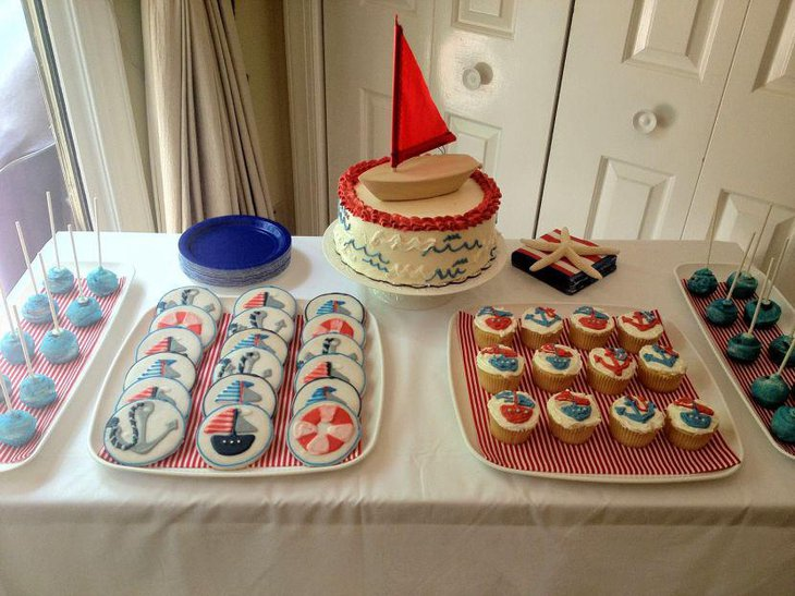 Nautical baby shower table decor with sail boat cake and cookies