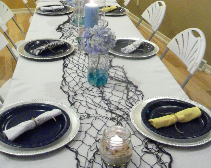 Nautical baby shower table setting with net and mason jars