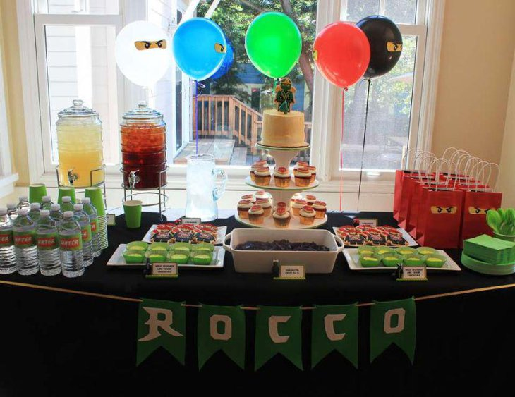Ninjago birthday party table with Ninjago figurine on cake and decorative goodie packets