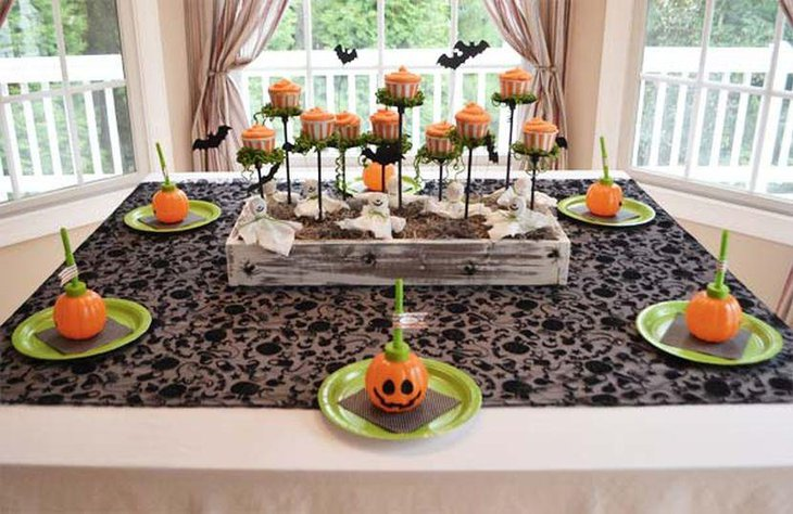 Orange kids Halloween table with pumpkins and cupcakes replicas