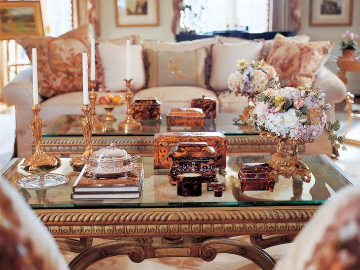 Ornately carved candleholders and flower bouquet as coffee table centerpiece