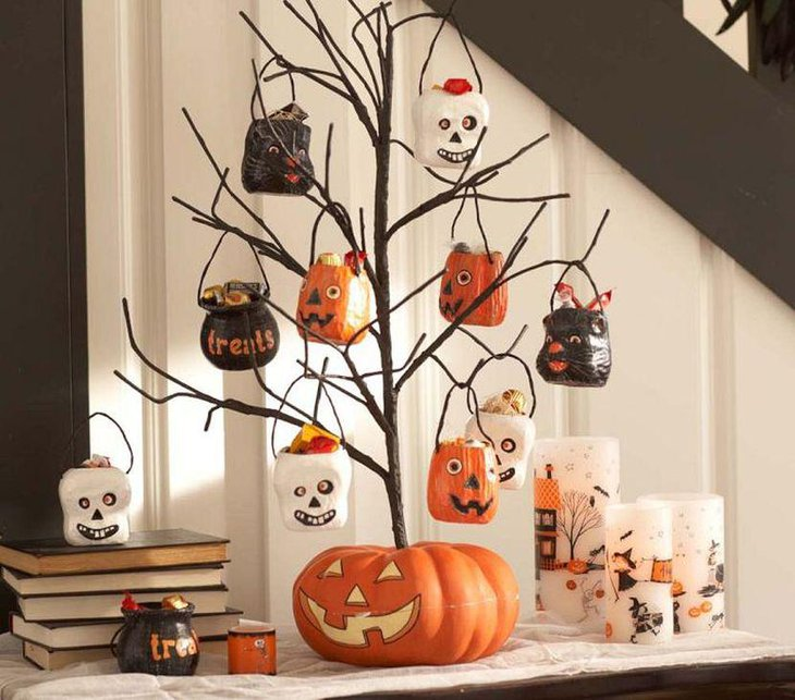 Outstanding DIY branch with hanging scary pots as Halloween table centerpiece