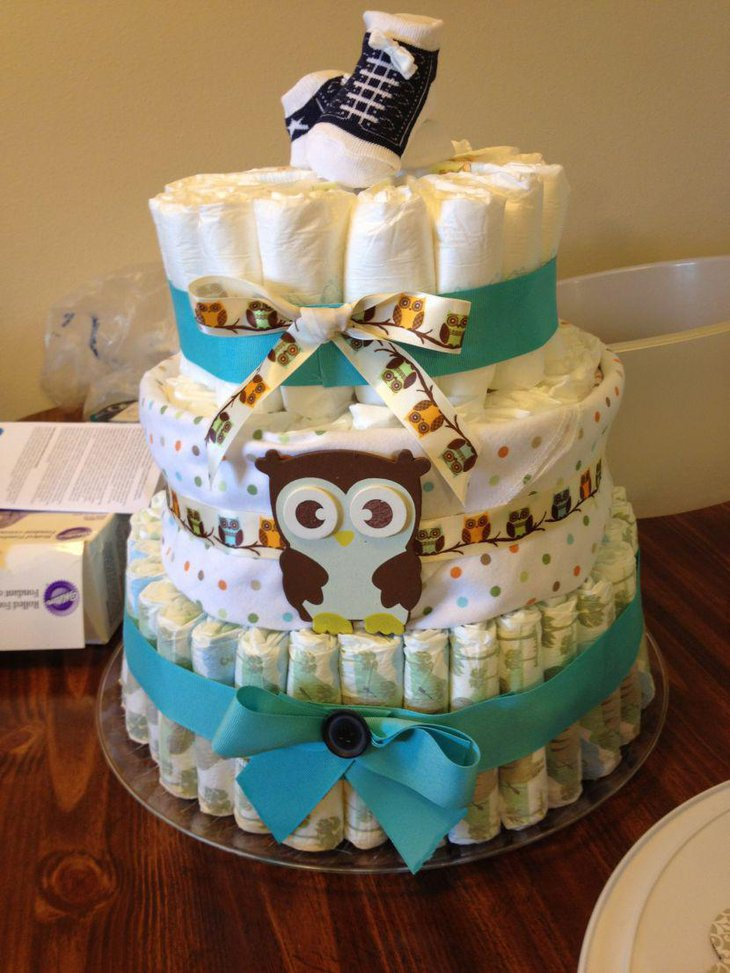 Owl diaper cake centerpiece wrapped with blue ribbon