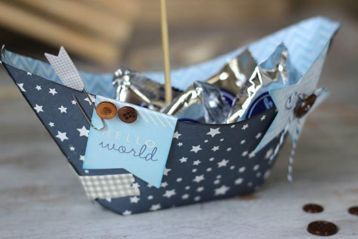 Paper sailboat centerpiece for nautical themed baby shower table
