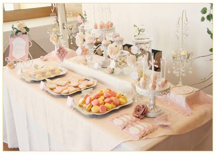 Pastel themed European dessert table laid out with cupcakes and cake pops