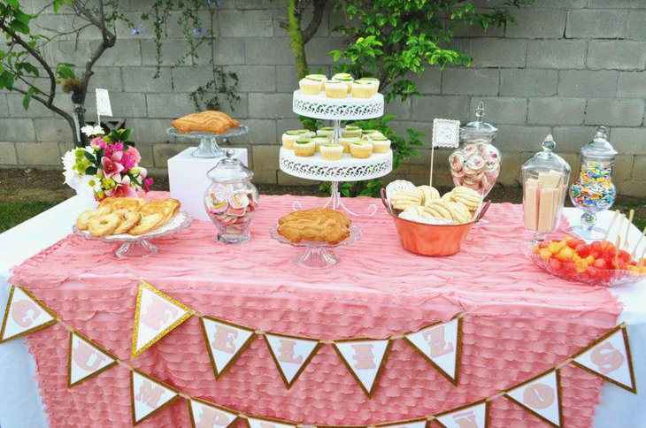 Pink and white floral decor seen on this 80th birthday dessert table