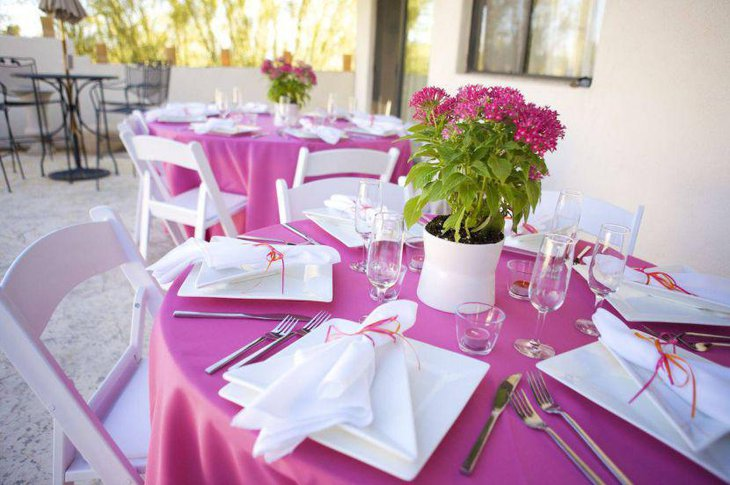 Pink and white wedding table setup with pink floral arrangement